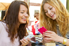 Two girls with smart phone. Two modern grils a cafe with smart phone Stock Photo