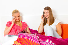 Two girls with smart phones. Lying in bed Royalty Free Stock Photos