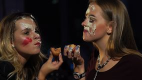 Two girls smear their faces with cake and have fun. Girls at the party smear cake on the face stock footage
