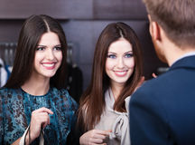 Two girls smiles at shop assistant. Two young women smiles at shop assistant Stock Photography