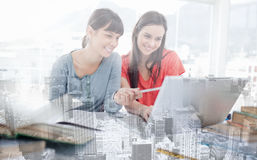 Two girls smiling as they use the laptop as one girl points at something Royalty Free Stock Photo