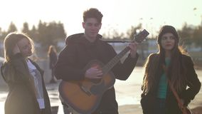 Two girls smiling while guy playing on the guitar at the sunset outdoors. Close up stock footage