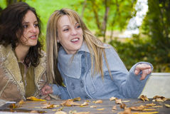 Two girls smiling and pointing Royalty Free Stock Image