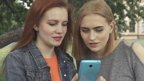 Girls smiling ang talking while sharing the phone. Two girls smiling and serfing the net on one`s smartphone. They comment what they see and the redhaired one stock video