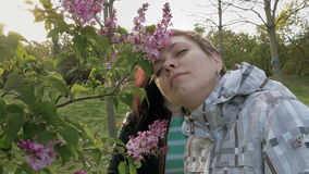 Two girls sniffing lilac flowers in the green park. Two pretty girls or young women sniffing smelling at lilac flowers in the green park in spring. Togetherness stock footage