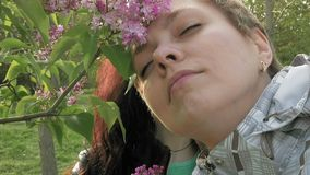 Two girls sniffing lilac flowers in the green park. Two pretty girls or young women sniffing smelling at lilac flowers in the green park in spring. Togetherness stock video footage