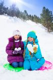 Two girls with snow hearts Stock Photo