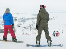 Two girls (snowboarder) are standing on the snowy background. Stock Image