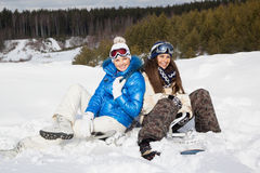 Two girls with snowboards sitting on the snow Royalty Free Stock Photo
