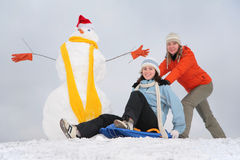 Two girls with snowman Stock Image