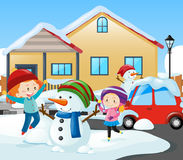 Two girls and snowman in front of the house Royalty Free Stock Photo