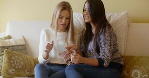 Two girls on sofa listen to the music. On mobile phone stock footage