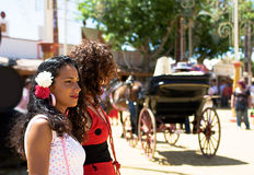 Two girls at the spanish fair. Two girls at spanish fair watch horse and carriage pass by with sherry casks in background stock photography
