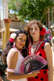 Two girls at the spanish fair. Two girls fanning themselves at the local spring fair in Andalusia, Spain Royalty Free Stock Image
