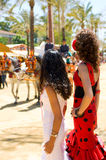 Two girls at the spanish fair. Two girls fanning themselves at the local spring fair in Andalusia, Spain. They are looking towards a traditional horse drawn Stock Image