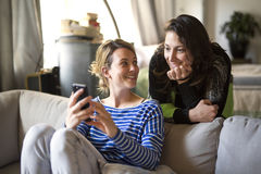 People relations. Two girls are speaking and using cellphone on sofa Royalty Free Stock Images