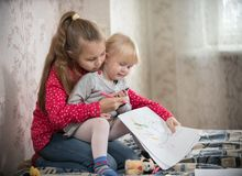 Two girls spending time at home drawing with markers stock photos