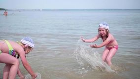 Two girls splash water on the beach. Twins pour water on a hot summer day, laughter and good mood of children. Twins pour water on a hot summer day, laughter and stock video footage