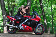 Two girls on a sport bike. Girls ride a sport bike in the woods. One is pressed against the other Royalty Free Stock Photography