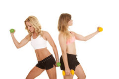 Two girls sports bras curl weights Royalty Free Stock Images