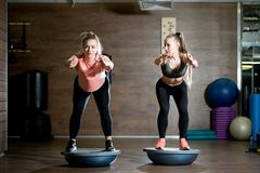 Two girls in a sports club are engaged with bosu