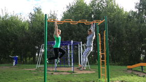 Two girls on sports ground. Two girls on sports ground making leg-split in the air hanging on sport equipment stock video footage