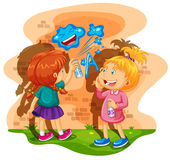 Two girls spray painting the wall Royalty Free Stock Photography