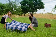 Two girls  spreading a blanket for picnic Stock Image