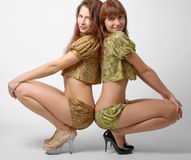 Two girls squatting down, side view Stock Photos