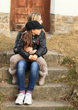 Two girls on stairs. Young women sitting on concrete stairs with a little girl on knees Stock Photos