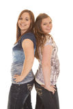 Two girls stand back to back Stock Images
