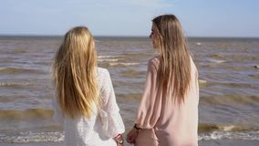 Two girls stand on the beach smiling laughing and talking on the background of coastal waves. Two blonde girls stand on the beach smiling laughing and talking on stock video footage