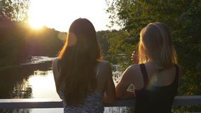 Two girls stand on the bridge at sunset and talk. Two young women chatting in the park standing on a bridge at sunset with beautiful glare on the water stock footage