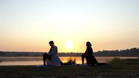 Two Girls Stand on Mats And Stretch Out Doing Forward Lunges at Sunset. Two Young Women Stand on Mats, Relax and Stretch Out Doing Forward Lunges at an Orange stock footage