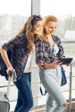 Two girls stand with suitcases at the airport and looking at the tablet. A trip with friends Royalty Free Stock Image