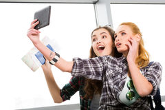 Two girls stand with suitcases at the airport and looking at the tablet. A trip with friends Stock Image