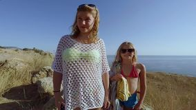 Two girls stand with their backs to the cliff beyond which extends sea stock video