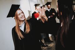 Two girls are standing in the corridor of the university in thei. Cheerful Celebration. Cap Architecture Happiness Asian Girl. Intelligence Diploma Standing royalty free stock images