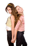 Two girls standing and embracing hands. Two girls in the age of ten and eleven standing and embracing hands isolated on white Stock Photo
