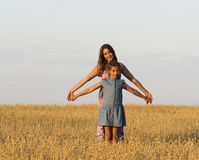Two girls is standing in a field. Royalty Free Stock Images