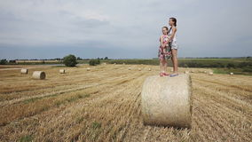 Two girls standing on haystack stock video footage