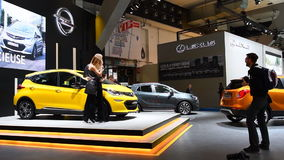 Two girls standing next to the Opel Ampera-e compact full electric car. While a man is taking pictures during the 2017 European Motor Show Brussels stock video footage