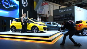 Two girls standing next to the Opel Ampera-e compact full electric car. While a man is taking pictures during the 2017 European Motor Show Brussels stock video