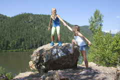 Two girls standing on a rock and enjoying river Royalty Free Stock Photography
