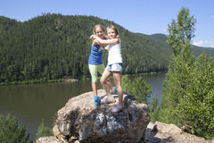 Two girls standing on a rock and enjoying river Stock Photo