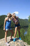 Two girls standing on a rock and enjoying river Stock Image