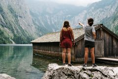 Two girls standing on top of a rock and wooden cottage in beauti. Ful lake in the Alps with misty mood Stock Photography