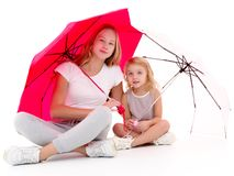 Two girls are standing under umbrellas. stock images