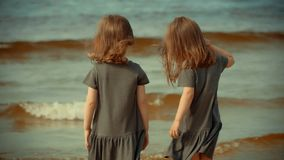 Two girls are standing in the water on a beach in summer. Two little girls are standing in the water on a beach by the sea in summer stock video