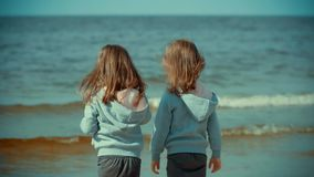 Two girls are standing in the water on a beach in summer. Two little girls are standing in the water on a beach by the sea in summer stock footage